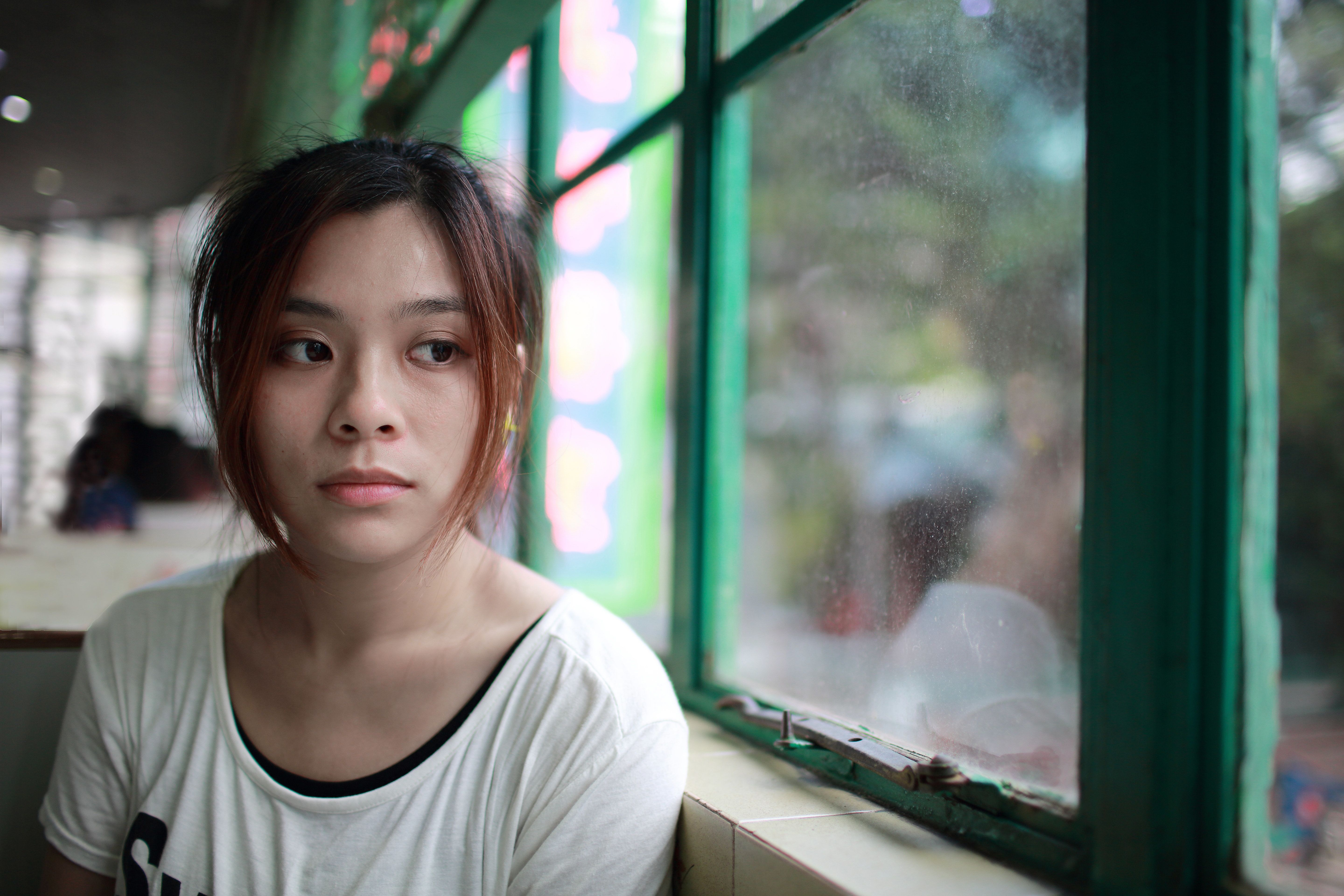 Sad woman waiting someone who is late, beside the window, in restaurant of Hong Kong