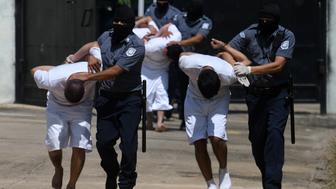 Handcuffed inmates, members of MS-13 and Barrio 18 gangs, are escorted upon arrival at the maximum security prison in Zacatecoluca, 65 km east of San Salvador, on August 30, 2017. Thirty-five members of violent gangs arrested in connection with the murders of policemen and soldiers, were transferred on August 30 to Zacatecoluca, the Salvadoran authorities reported. / AFP PHOTO / MARVIN RECINOS        (Photo credit should read MARVIN RECINOS/AFP/Getty Images)