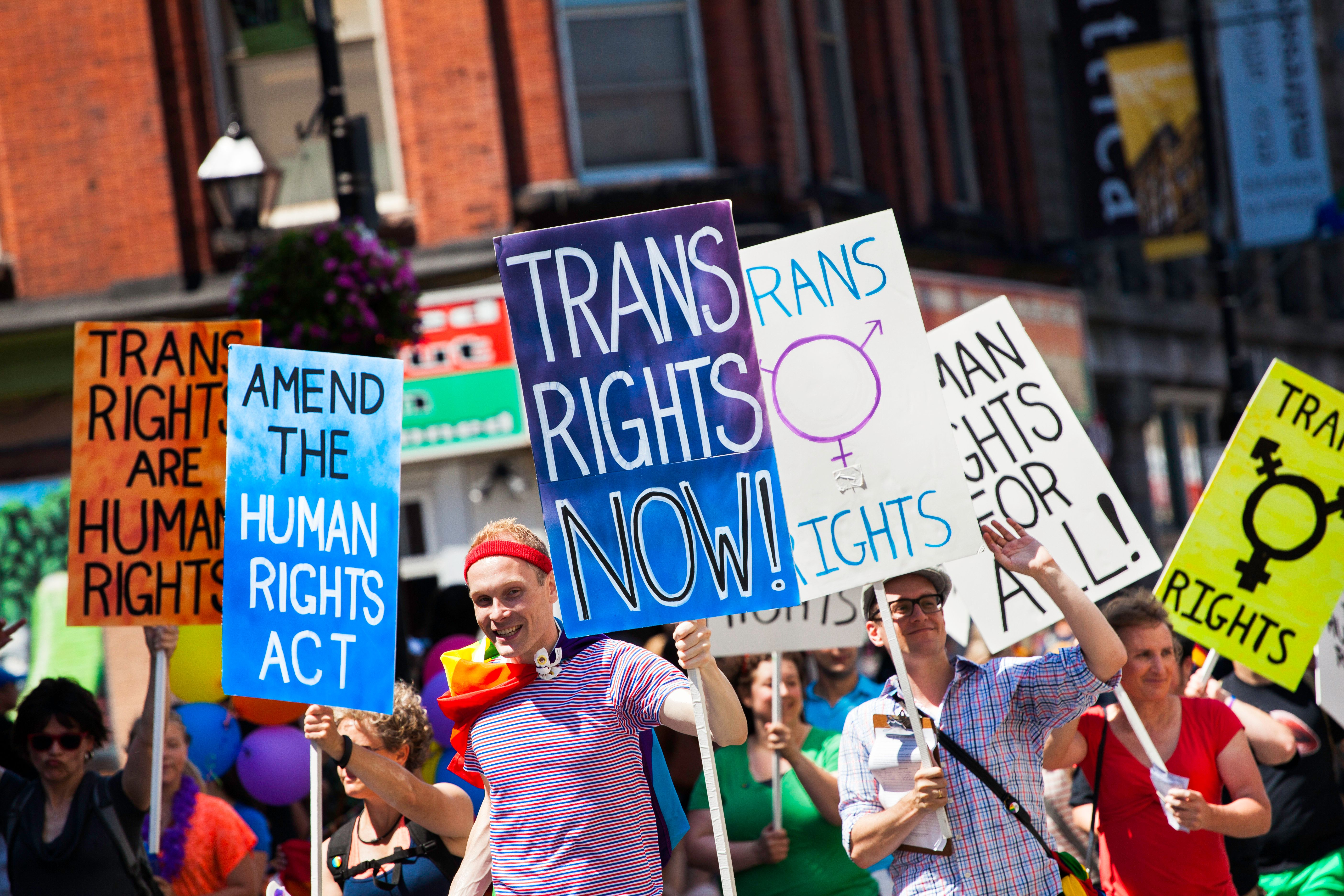 Halifax, Nova Scotia, Canada - July 28, 2012: Participants in the Halifax Pride Parade hold numerous signs as they walk down Barrington Street in the downtown district.  Signs include, 'Trans Rights Now', 'Amend the Human Rights Act', and 'Human Rights for All' among others.  Participants smile and some wave to the crowd.  Downtown business visible in background.  The Halifax Pride Parade has over 150 floats and continues through the downtown area of Halifax, Nova Scotia.