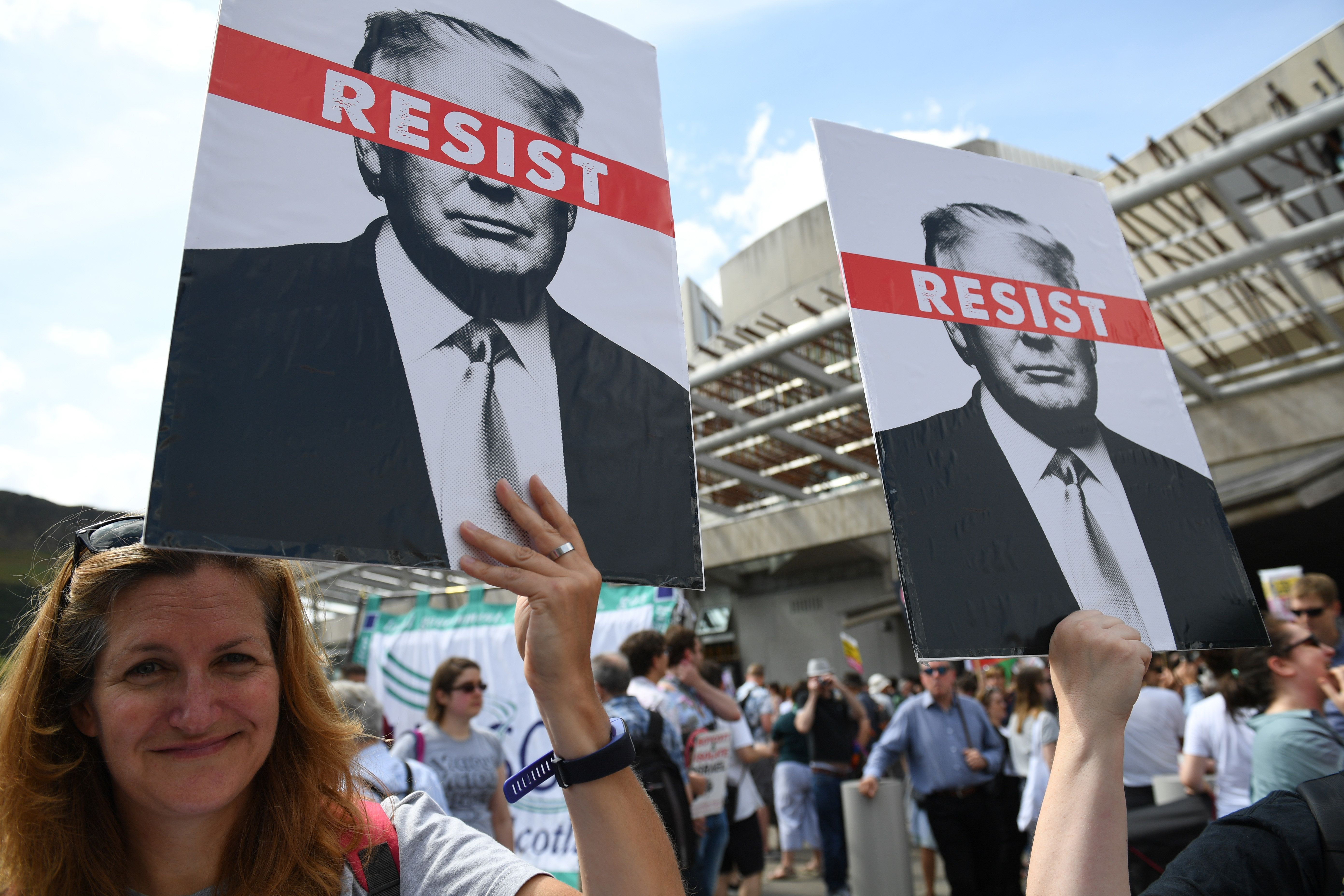 EDINBURGH, SCOTLAND - JULY 14:  People hold anti-Trump signs while the U.S. President is visiting Trump Turnberry Luxury Collection Resort in Scotland as people gather to protest during his visit to the United Kingdom on July 14, 2018 in Edinburgh, Scotland. The President of the United States and First Lady, Melania Trump on their first official visit to the UK after yesterday's meetings with the Prime Minister and the Queen is in Scotland for private weekend stay at his Turnberry.  (Photo by Jeff J Mitchell/Getty Images)