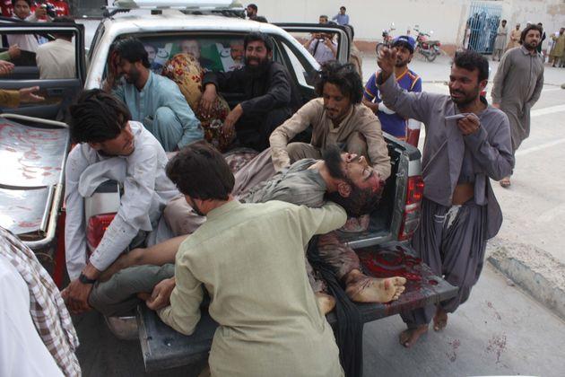 Des personnestransportant les blessésvers l'hôpital, après l'attentant...