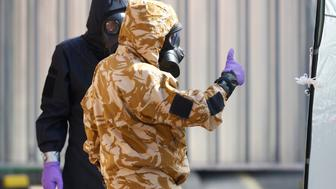 Forensic investigators, wearing protective suits, emerge from the rear of John Baker House, after it was confirmed that two people had been poisoned with the nerve-agent Novichok, in Amesbury, Britain, July 6, 2018. REUTERS/Henry Nicholls