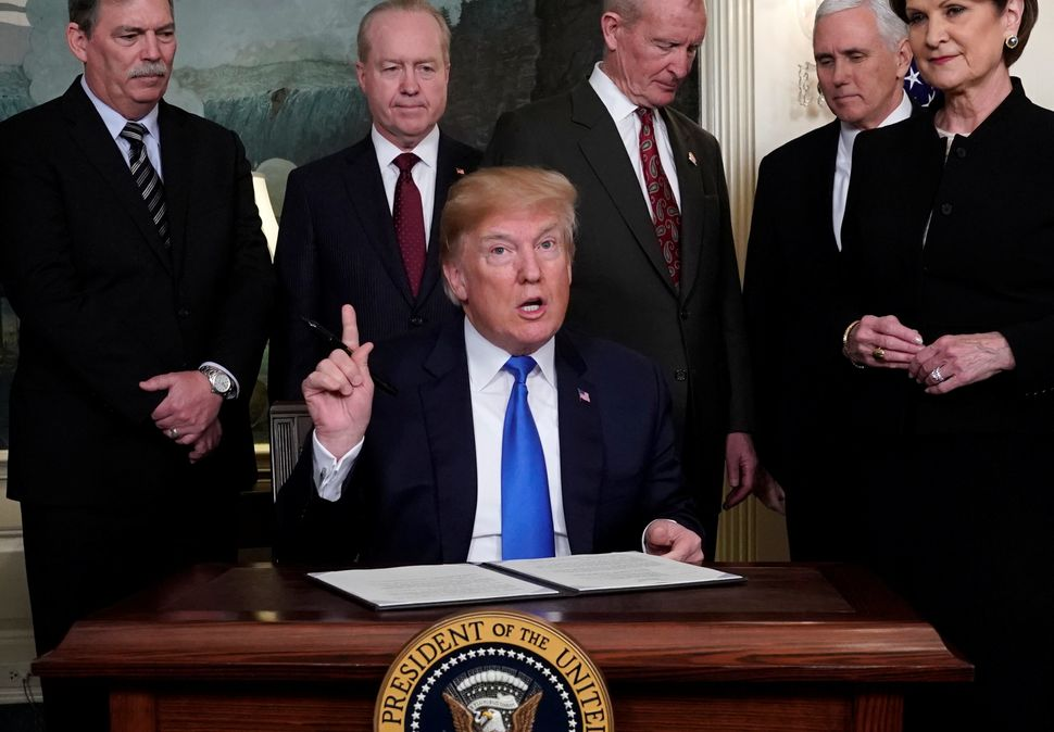 U.S. President Donald Trump, surrounded by business leaders and administration officials, prepares to sign a memorandum on in