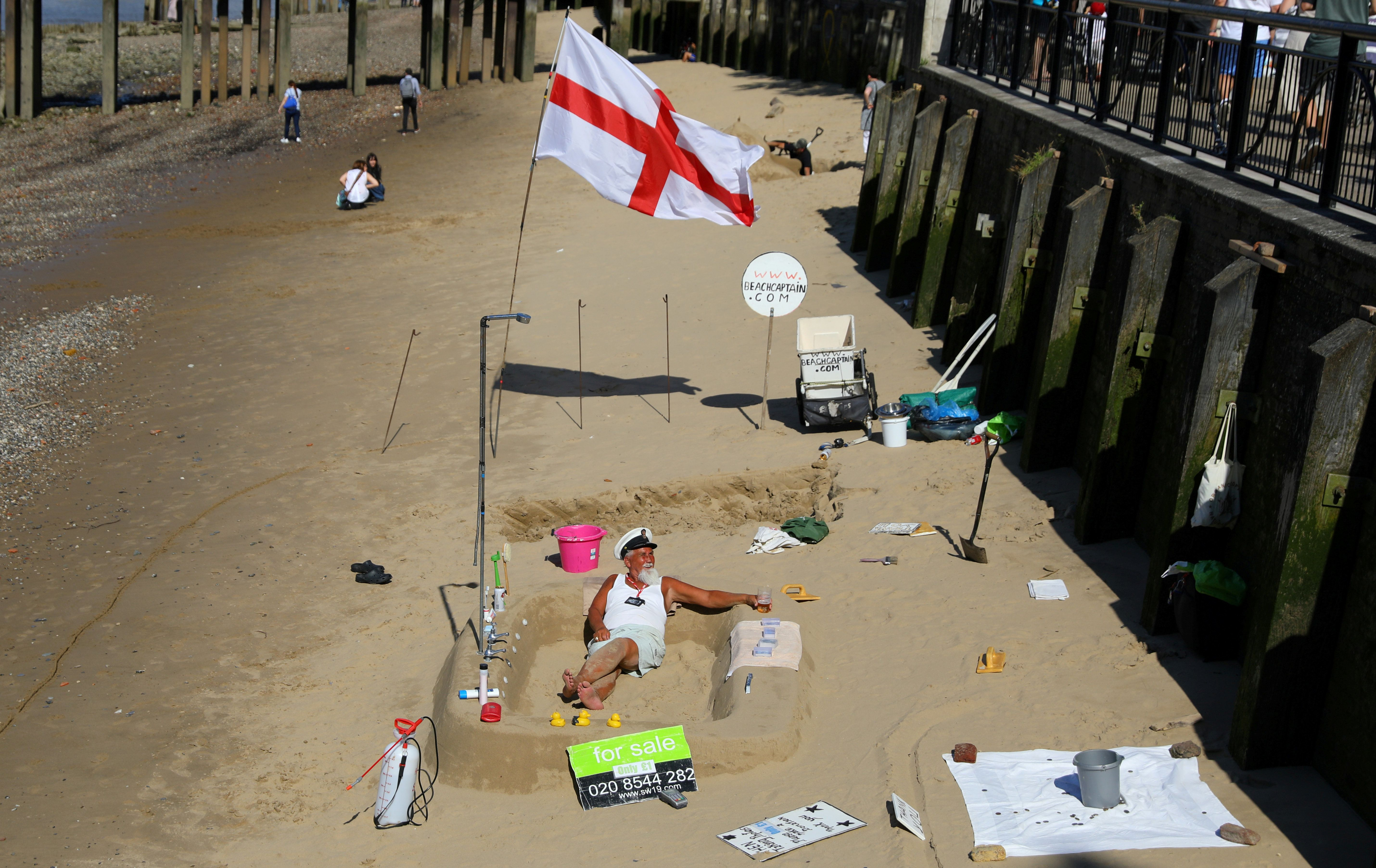 A man sits on the sand of a beach revealed by a low tide of the River Thames.