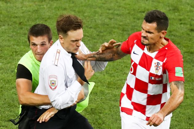 Croatia's Dejan Lovren shoves a man who invaded the field during the World Cup final's second