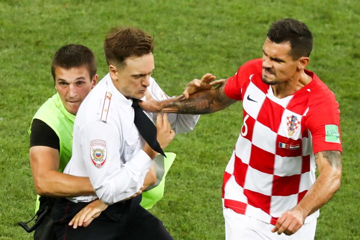 Croatia's Dejan Lovren shoves a man who invaded the field during the World Cup final's second half.