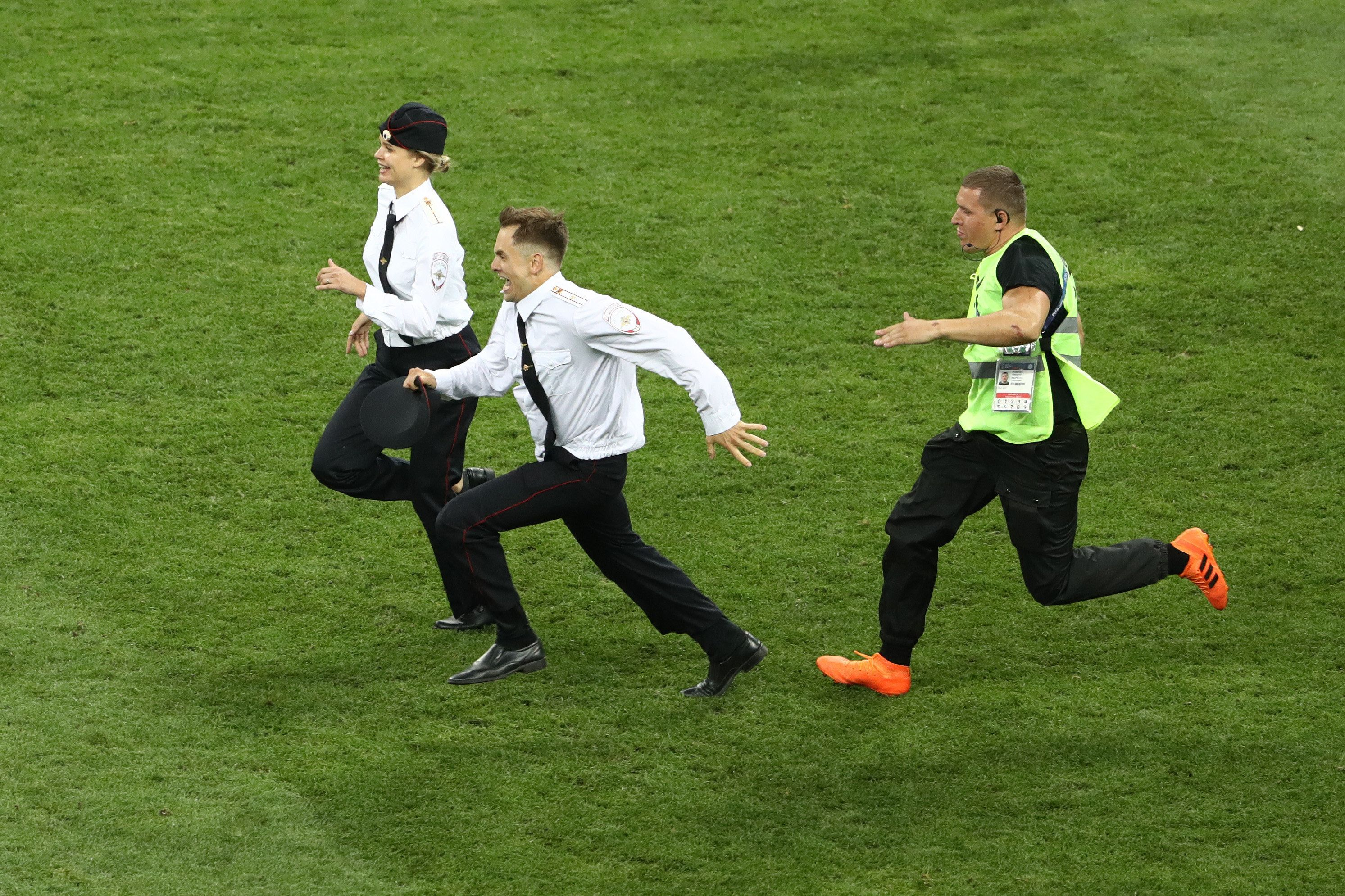A man and woman are seen being chased by guards after invading the field at the World Cup final