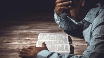 Worried man reading the Holy Bible.
