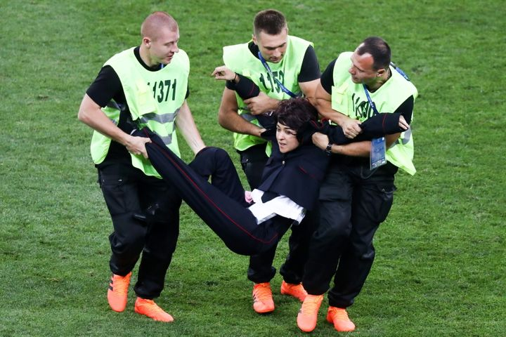 Security guards detain a field invader during the 2018 FIFA World Cup final match between France and Croatia at Luzhniki