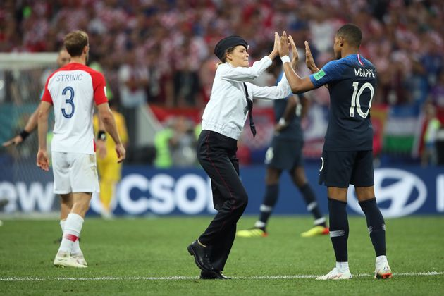 A woman high-five's Kylian Mbappe of France after running onto the