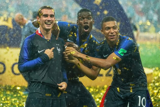 Kylian Mbappe, Antoine Griezmann and Paul Pogba show off the two stars on their shirts, signifying a...