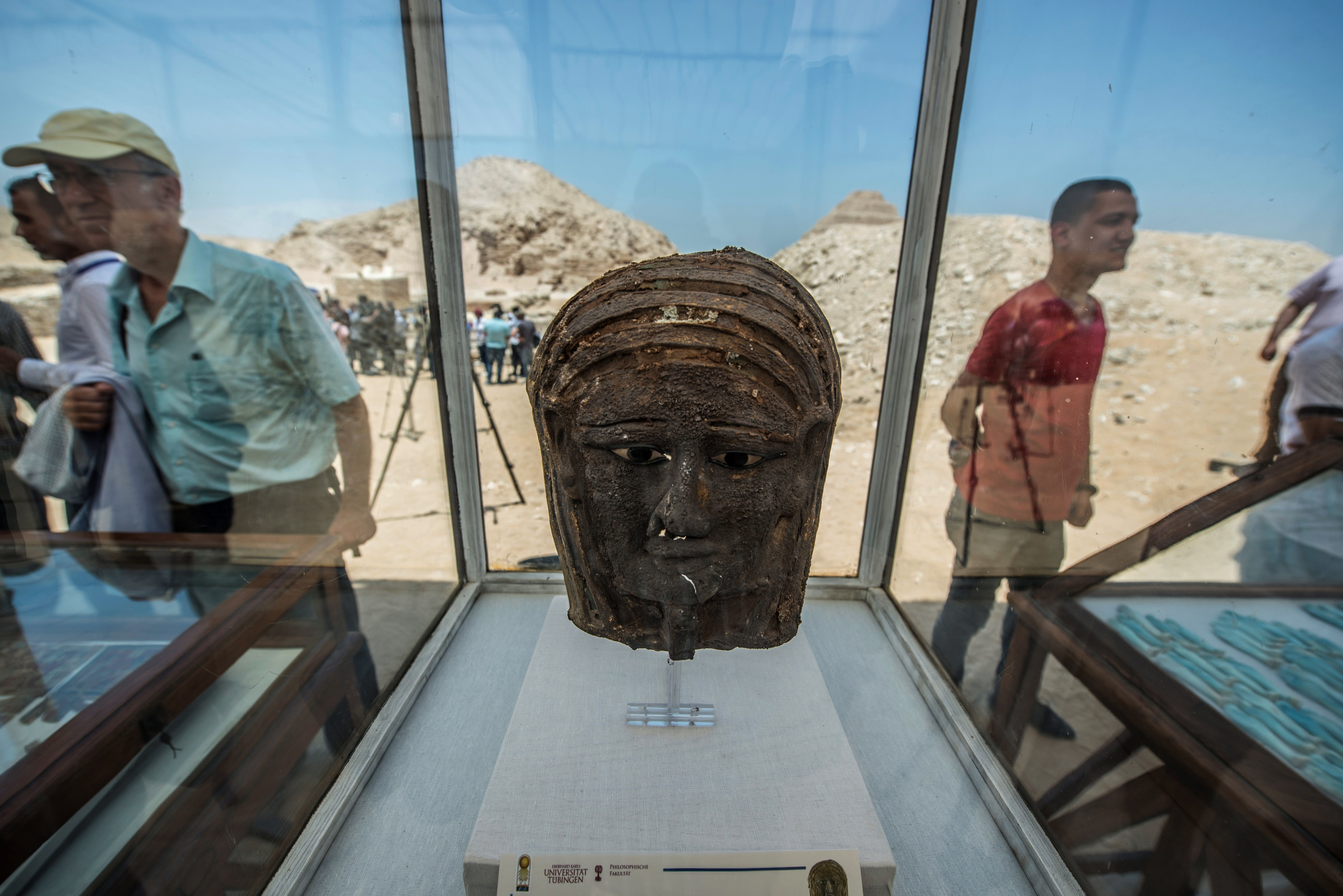 A picture taken on July 14, 2018 shows a gilded silver mummy mask found on the face of the mummy of the second priest of Mut on display in front of the step pyramid of Saqqara, south of the Egyptian capital Cairo. - Egypt's Ministry of Antiquities announced on July 14 the excavation of a mummification workshop discovered along with a communal burial place consisting of several burial chambers. The excavation is carried out by a Egyptian-German mission at the Saqqara necropolis complex south of the King Unas Pyramid. (Photo by Khaled DESOUKI / AFP)        (Photo credit should read KHALED DESOUKI/AFP/Getty Images)