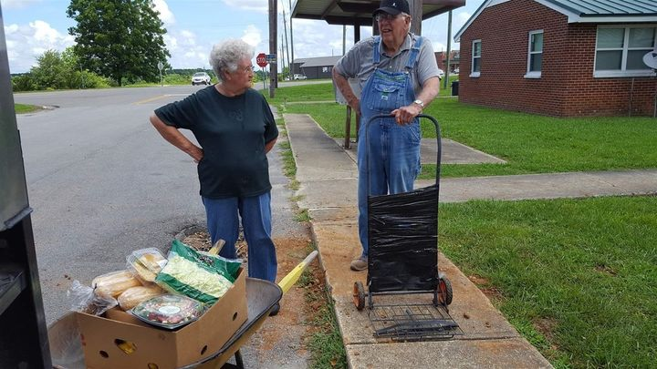 Nellie Allen, 81, left, and O'Neal West, 78, of Hackleburg, Alabama, load donated groceries into a wheelbarrow and a makeshif