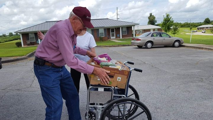 John Seals, 83, of Hackleburg, Alabama, uses a wheelchair to carry a box of food from a West Alabama Food Bank truck.