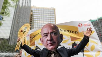 BERLIN, GERMANY - 2018/04/24: A demonstrator of a Jeff Bezos holds a Symbolic Award in the air during the demonstration against the awarding of the Axel Springer Award 2018 to Amazon founder Jeff Bezos for his 'visionary entrepreneurship'. Employees of the company demonstrated under the motto 'Make Amazon Pay Again' against the Axel Springer Award the outstanding personalities, according to the media company, who are particularly innovative, create and change markets and face up to their social responsibility. Trade unions criticize the poor working conditions in Amazon's logistics centers, which they do not consider worthy of praise. (Photo by Markus Heine/SOPA Images/LightRocket via Getty Images)