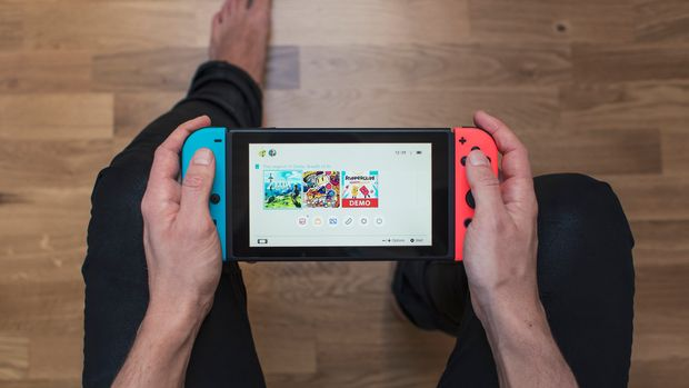 Gothenburg, Sweden - March 10, 2017: A shot from above of a young man's hands holding a neon coloured Nintendo Switch video game system developed and released by Nintendo Co., Ltd. in 2017. The system is turned on and its main menu is showing on the display. Shot on a hardwood floor background in a home environment.