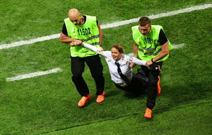 A pitch invader, a member of the Russian protest-art group Pussy Riot, is escorted by stewards during the Russia 2018 World C