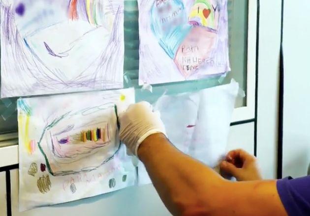 Ein Pfleger nimmt die Bilder ab, die die Kinder eines Patienten gemalt