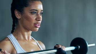 Shot of an attractive young woman lifting weights at the gym