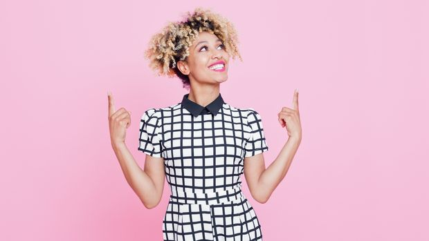 Studio portrait of happy afro american young woman pointing with index fingers at copy space. Pink background.