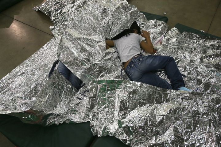 A girl from Central America rests on thermal blankets at a detention facility run by the U.S. Border Patrol on Sept. 8, 2014, in McAllen, Texas.