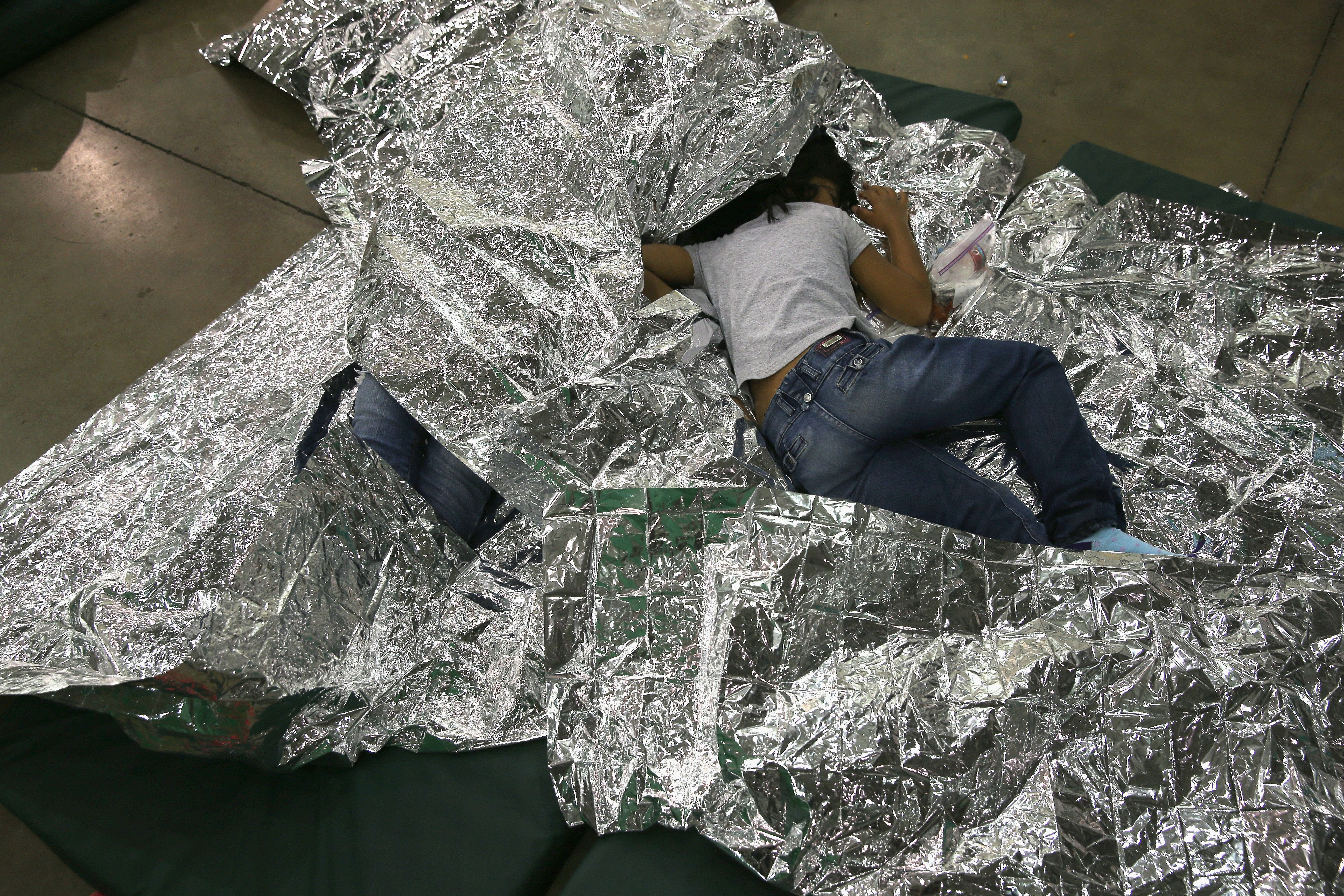 A girl from Central America rests on thermal blankets at a detention facility run by the U.S. Border Patrol on Sept. 8, 2014,