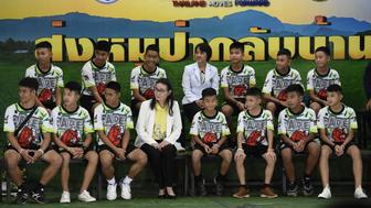 Twelve Thai boys and their football coach, rescued from a flooded cave after being trapped, attend a press conference in Chiang Rai on July 18, 2018, following their discharge from the hospital. - The young footballers and their coach appeared healthy when they appeared before the media for the first time on July 18. (Photo by LILLIAN SUWANRUMPHA / AFP)        (Photo credit should read LILLIAN SUWANRUMPHA/AFP/Getty Images)