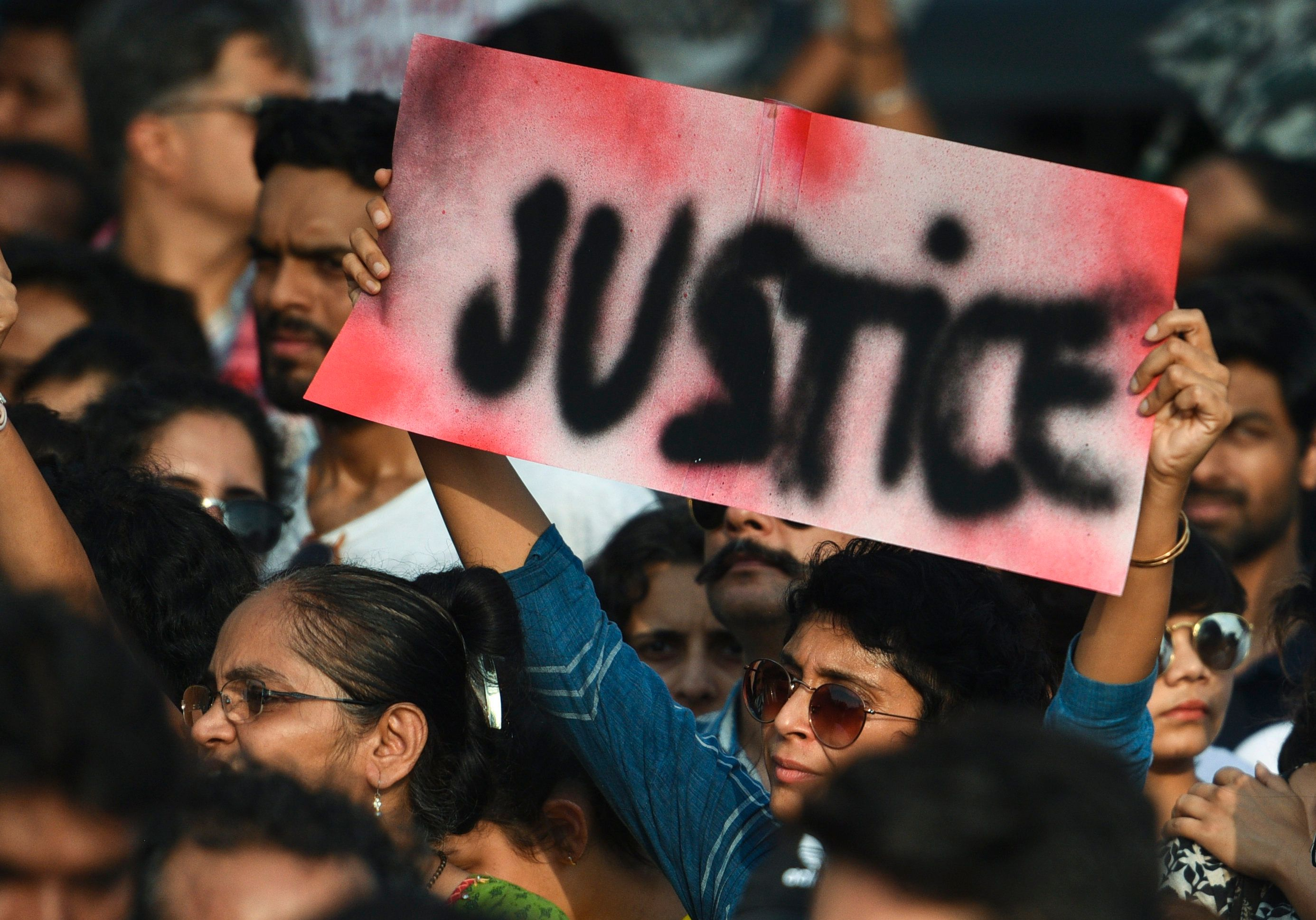 People hold signs as they participate in a protest against the Kathua,  Unnao,