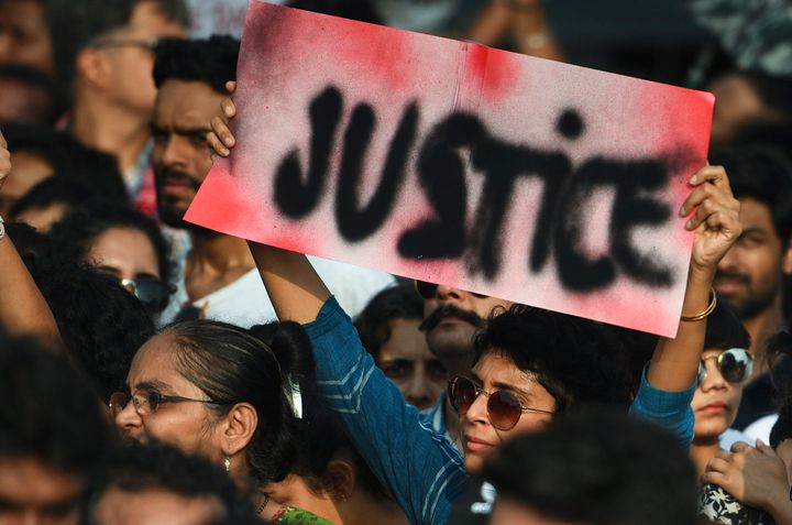 People hold signs as they participate in a protest against the Kathua, Unnao, rape cases and other incidents of rape in