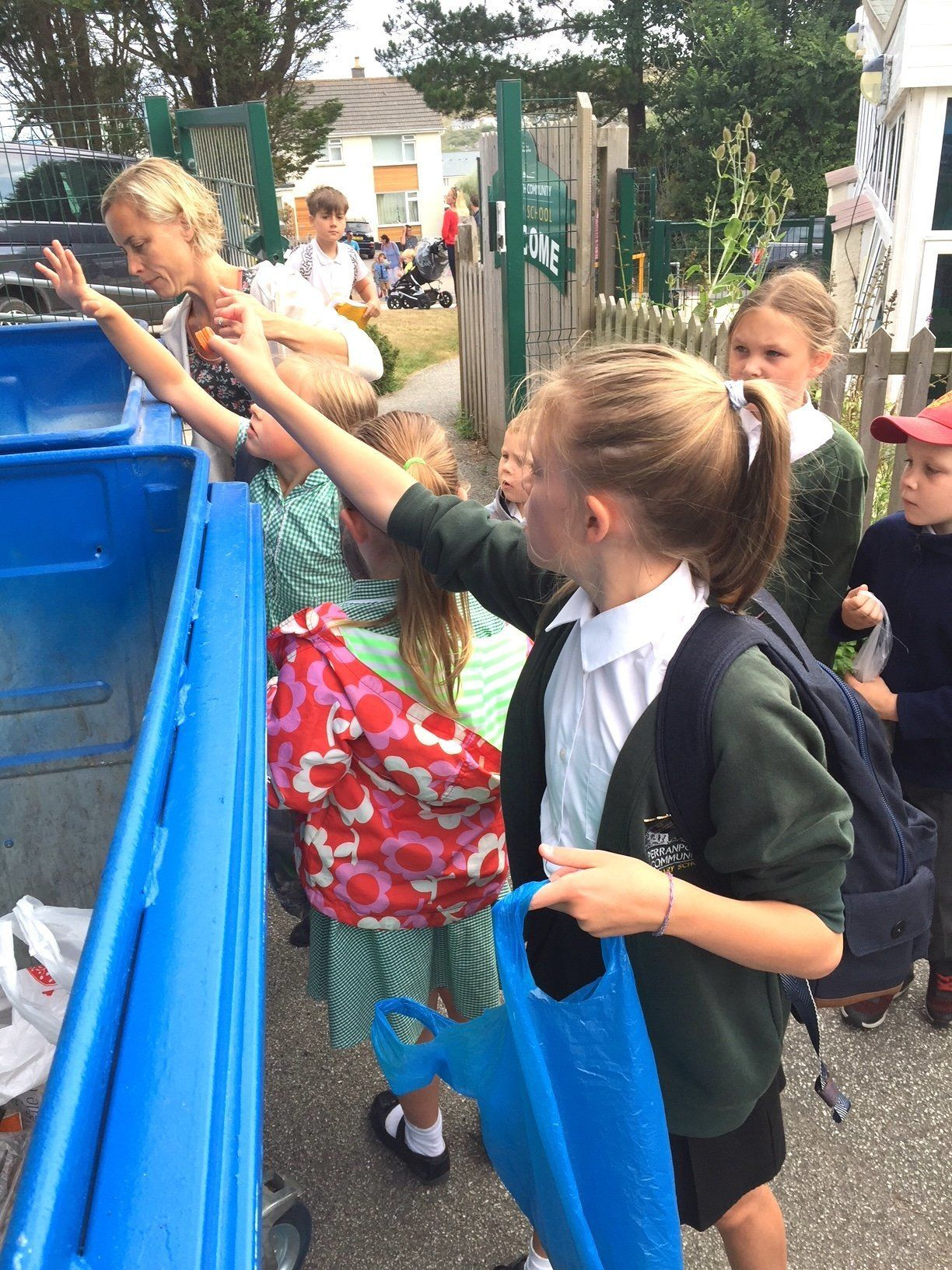 Primary school children dispose of what they've collected in their early morning litter