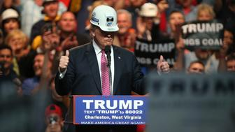 CHARLESTON, WV - MAY 05: Republican Presidential candidate Donald Trump models a hard hat in support of the miners during his rally at the Charleston Civic Center on May 5, 2016 in Charleston, West Virginia. Trump became the Republican presumptive nominee following his landslide win in indiana on Tuesday.(Photo by Mark Lyons/Getty Images)