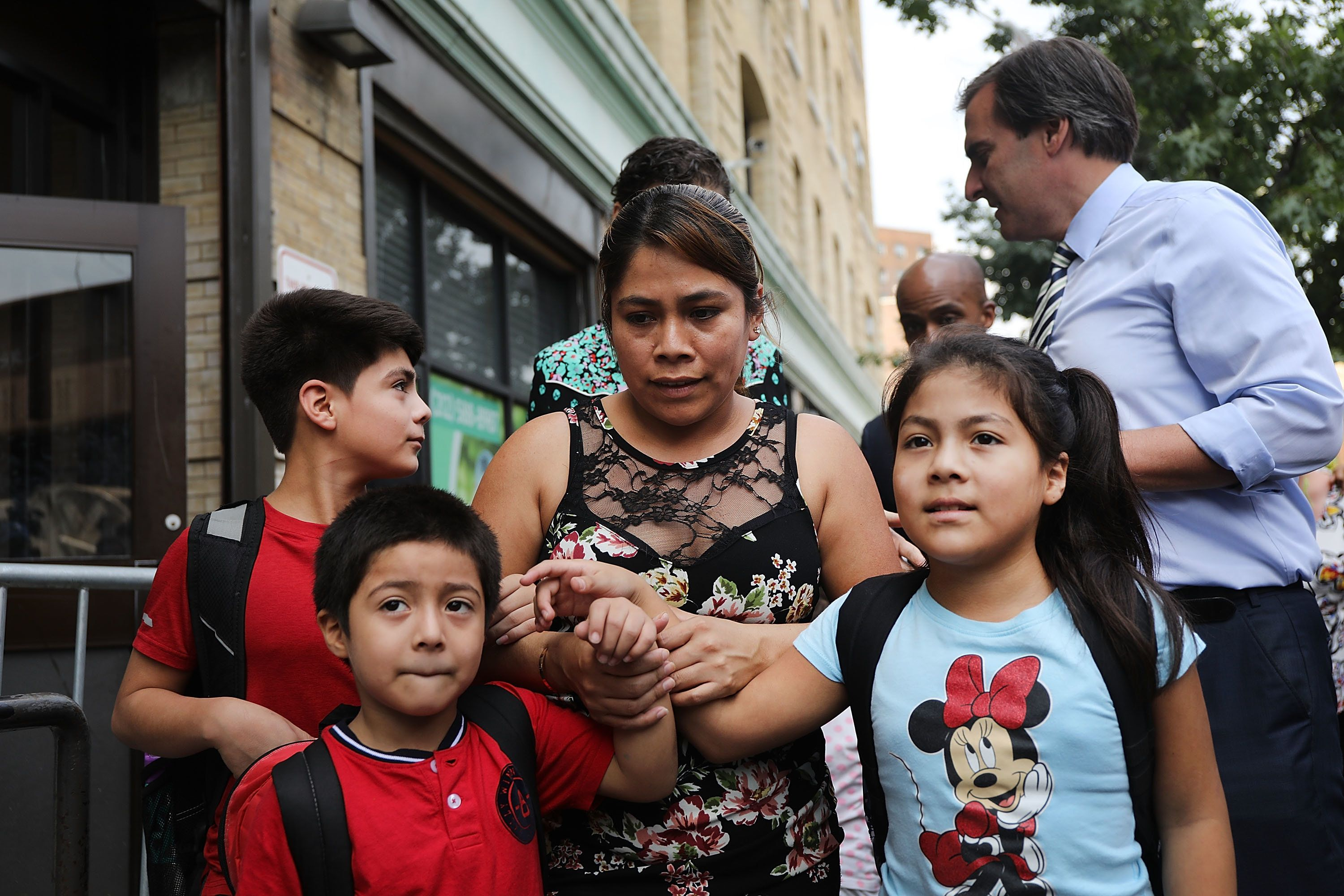 Yeni Maricela Gonzalez Garcia holds fast to 11-year-old Lester, left, 6-year-old Deyuin and, 9-year-old Jamelin and  as
