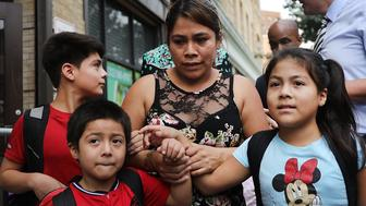 NEW YORK, NY - JULY 13:  Yeni Maricela Gonzalez Garcia (center) stands with her children 6 year-old Deyuin (left), 9 year-old Jamelin (right) and 11 year-old Lester (back) as she and her lawyer speak with the news media after she was reunited with her children at the East Harlem Cayuga Centers on July 13, 2018 in New York City. Gonzalez Garcia, from Guatemala, drove cross-country to be reunited with her three children after they were taken from an Arizona immigration facility over eight weeks ago. Gonzalez Garcia crossed over the U.S. border with her three children on May 19, only two days before they were taken from her as part of President Donald Trump's controversial zero-tolerance policy of removing immigrant children from their parents after they are detained.  (Photo by Spencer Platt/Getty Images)