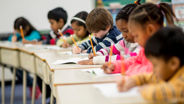 A multi-ethnic group of elementary school children are indoors in a classroom. They are wearing casual clothing. The students are sitting at their desks and writing with pencils.