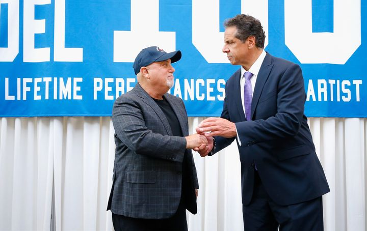 New York Gov. Andrew Cuomo (D), right, congratulates musician Billy Joel on his 100th show at Madison Square Garden in Manhat