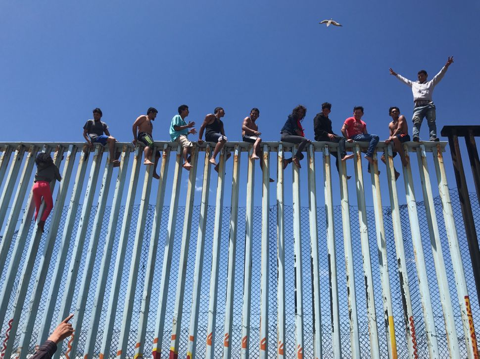 "Third Place<br>""Refugee Caravan""<br>Members of the Refugee Caravan 2017 climb the border fence dividing Mexico and the U.S. t"