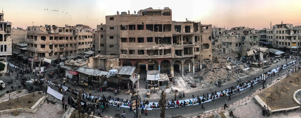 "First Place<br>""Iftar Amongst the Ruins""<br>During a lull in the bombings, Syrians gather, seated on a long 1200-meter row of"