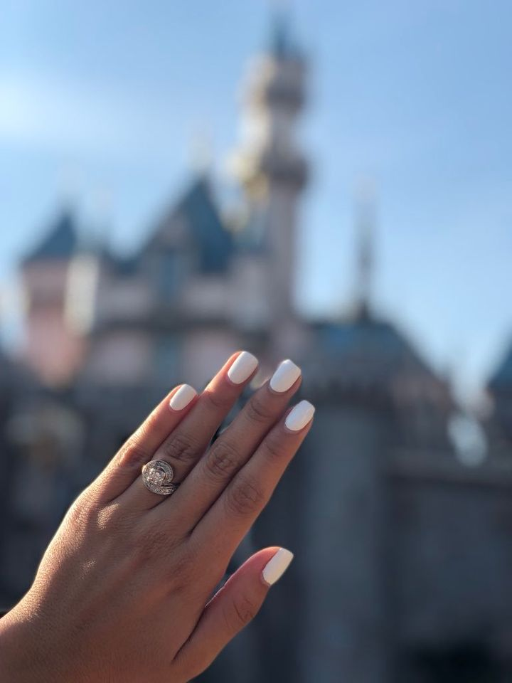 A photo of theengagement ring in front of Sleeping Beauty Castle at Disneyland.