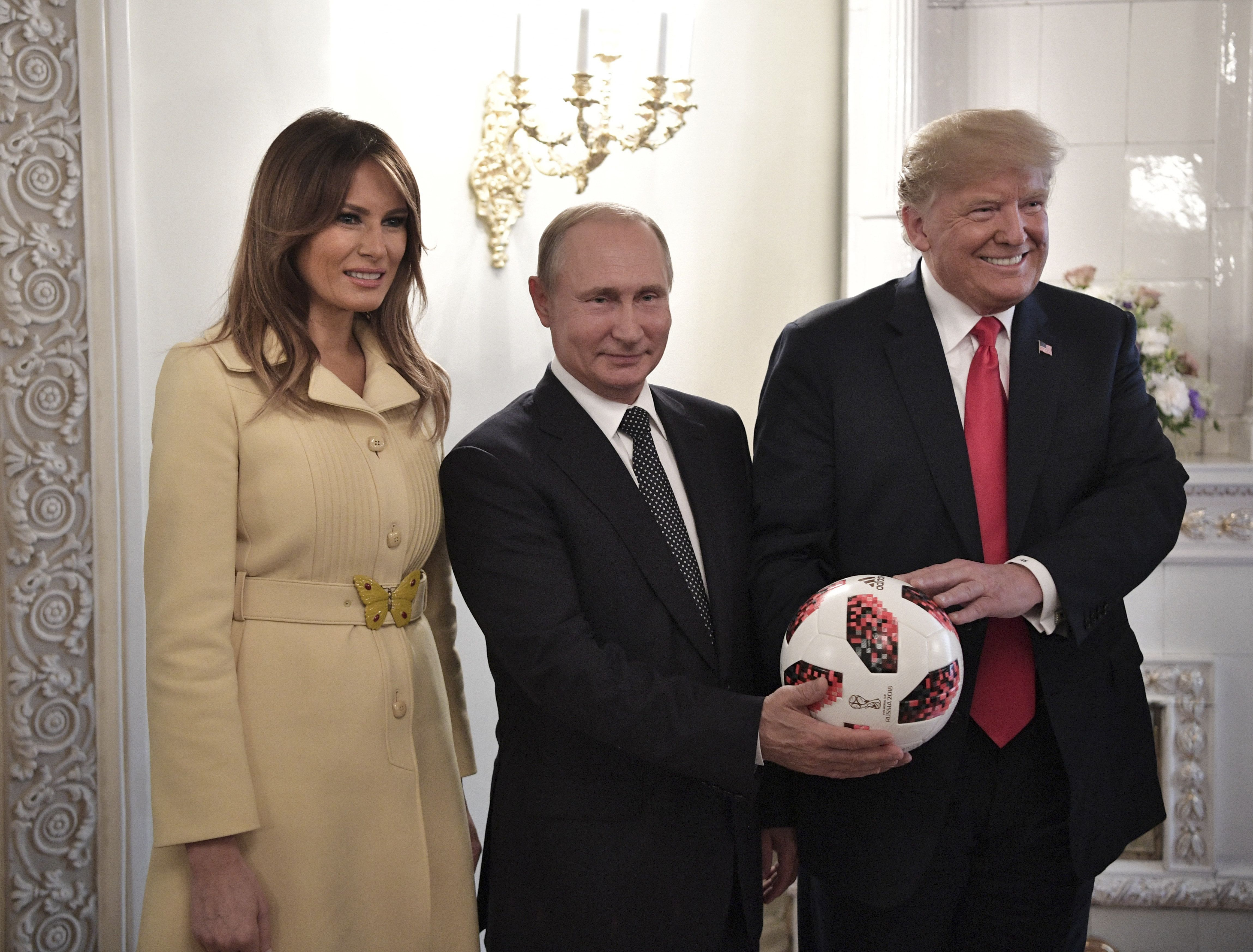 Russia's President Vladimir Putin (C), U.S. President Donald Trump (R) and First lady Melania Trump pose for a picture with a football during a meeting in Helsinki, Finland July 16, 2018. Sputnik/Alexei Nikolsky/Kremlin via REUTERS  ATTENTION EDITORS - THIS IMAGE WAS PROVIDED BY A THIRD PARTY.