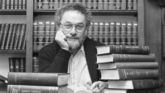 (Original Caption) February 1, 1988 - Philadelphia: Adrian Cronauer, the former Vietnam disk jockey that Robin Williams played in the box office smash Good Morning Vietnam, looks over the pile of law books at the University of Pennsylvania. Cronauer is studying law there after spending most of his life in broadcasting.