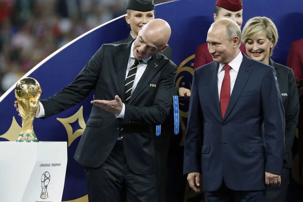 FIFA President Gianni Infantino, left, shows the World Cup trophy to Russian President Vladimir Putin after the final match i