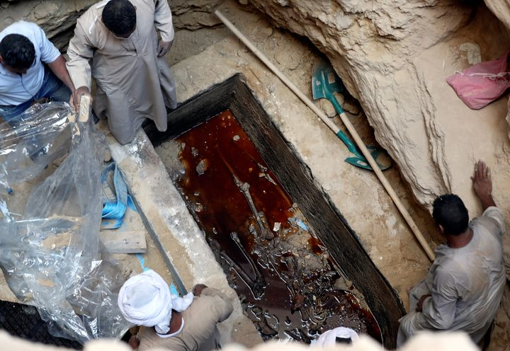 Workers open a coffin containing skeletal remains lying in sewage water in Alexandria, Egypt, on Thursday.