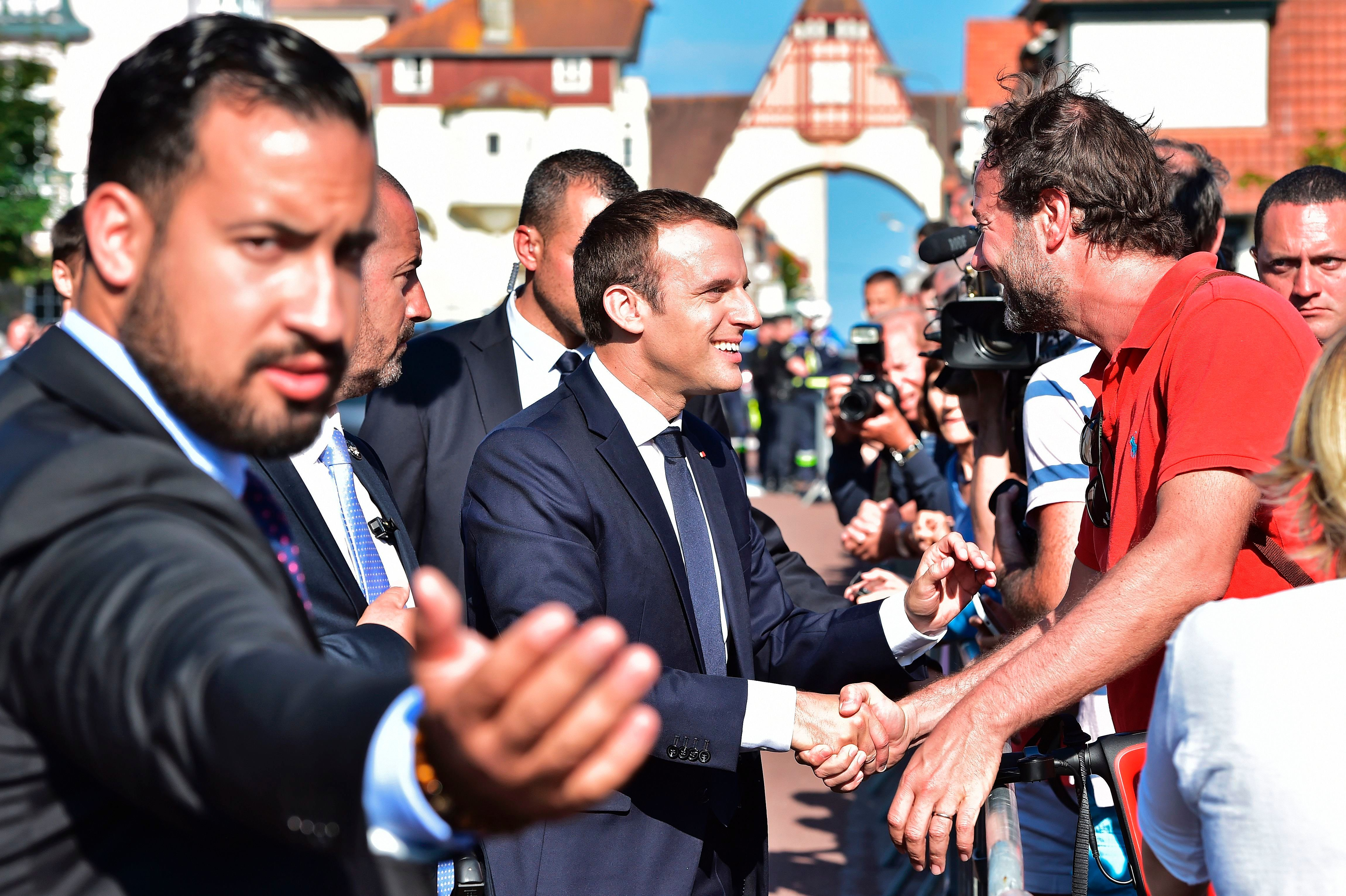 French President Emmanuel Macron (C), flanked by Elysee senior security officer Alexandre Benalla (L), shakes hands with people after he voting in Le Touquet, northern France, during the second round of the French parliamentary elections (elections legislatives in French), on June 18, 2017. (Photo by CHRISTOPHE ARCHAMBAULT / POOL / AFP)        (Photo credit should read CHRISTOPHE ARCHAMBAULT/AFP/Getty Images)
