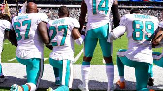 EAST RUTHERFORD, NJ - SEPTEMBER 24:  Laremy Tunsil #67, Maurice Smith #27 and Julius Thomas #89 kneel with Jarvis Landry #14 of the Miami Dolphins during the National Anthem prior to an NFL game against the New York Jets at MetLife Stadium on September 24, 2017 in East Rutherford, New Jersey.  (Photo by Steven Ryan/Getty Images)