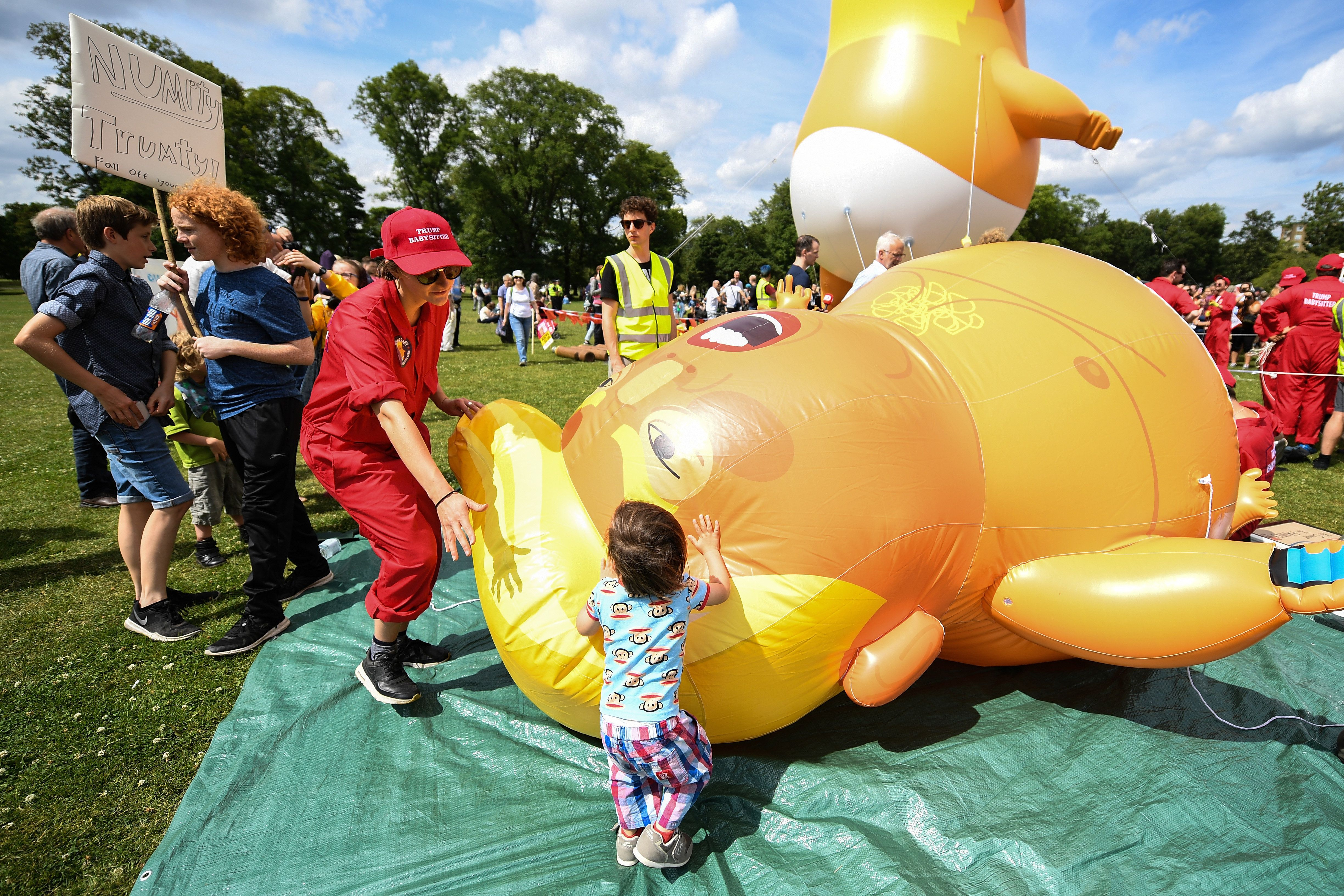 EDINBURGH, SCOTLAND - JULY 14:  The Baby Trump Balloon floats in the middle of crowds holding anti-Trump signs while the U.S. President is visiting Trump Turnberry Luxury Collection Resort in Scotland as people gather to protest during his visit to the United Kingdom on July 14, 2018 in Edinburgh, Scotland. The President of the United States and First Lady, Melania Trump on their first official visit to the UK after yesterday's meetings with the Prime Minister and the Queen is in Scotland for private weekend stay at his Turnberry.  (Photo by Jeff J Mitchell/Getty Images)