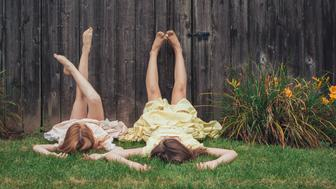 two sisters lying on the grass with their legs against the wooden fence with vintage dresses