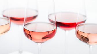Grouping of five varieties of rose wine in wineglasses.