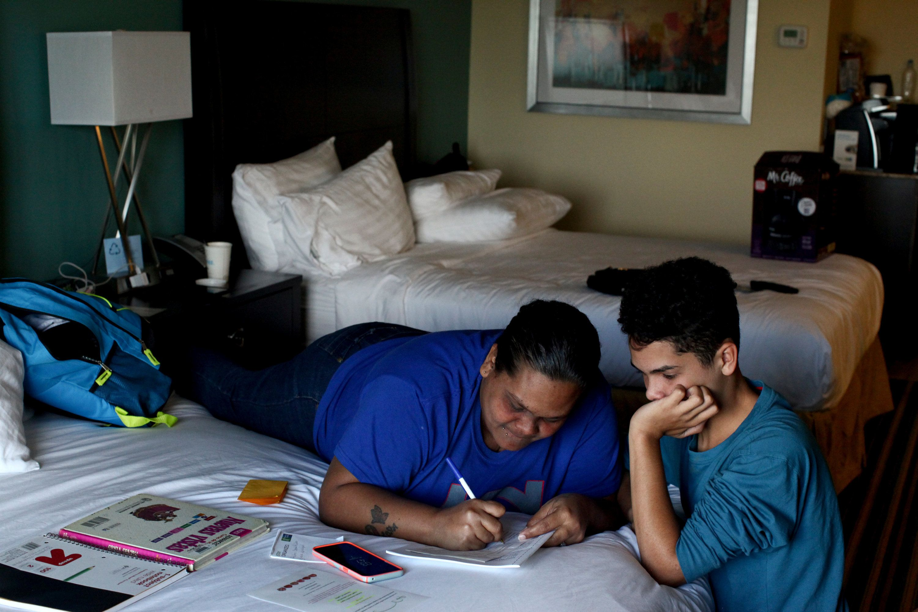 Liz Vazquez helps her son Raymond Fernandez Vazquez with his homework in an Orlando, Florida hotel room, where they've been l