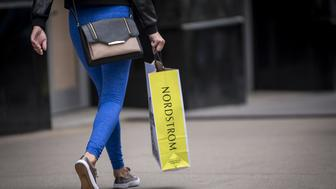 A shopper carries a Nordstrom Inc. bag in downtown Chicago, Illinois, U.S., on Friday, Aug. 4, 2017. Nordstrom Inc. is scheduled to release earnings figures on August 10. Photographer: Christopher Dilts/Bloomberg via Getty Images