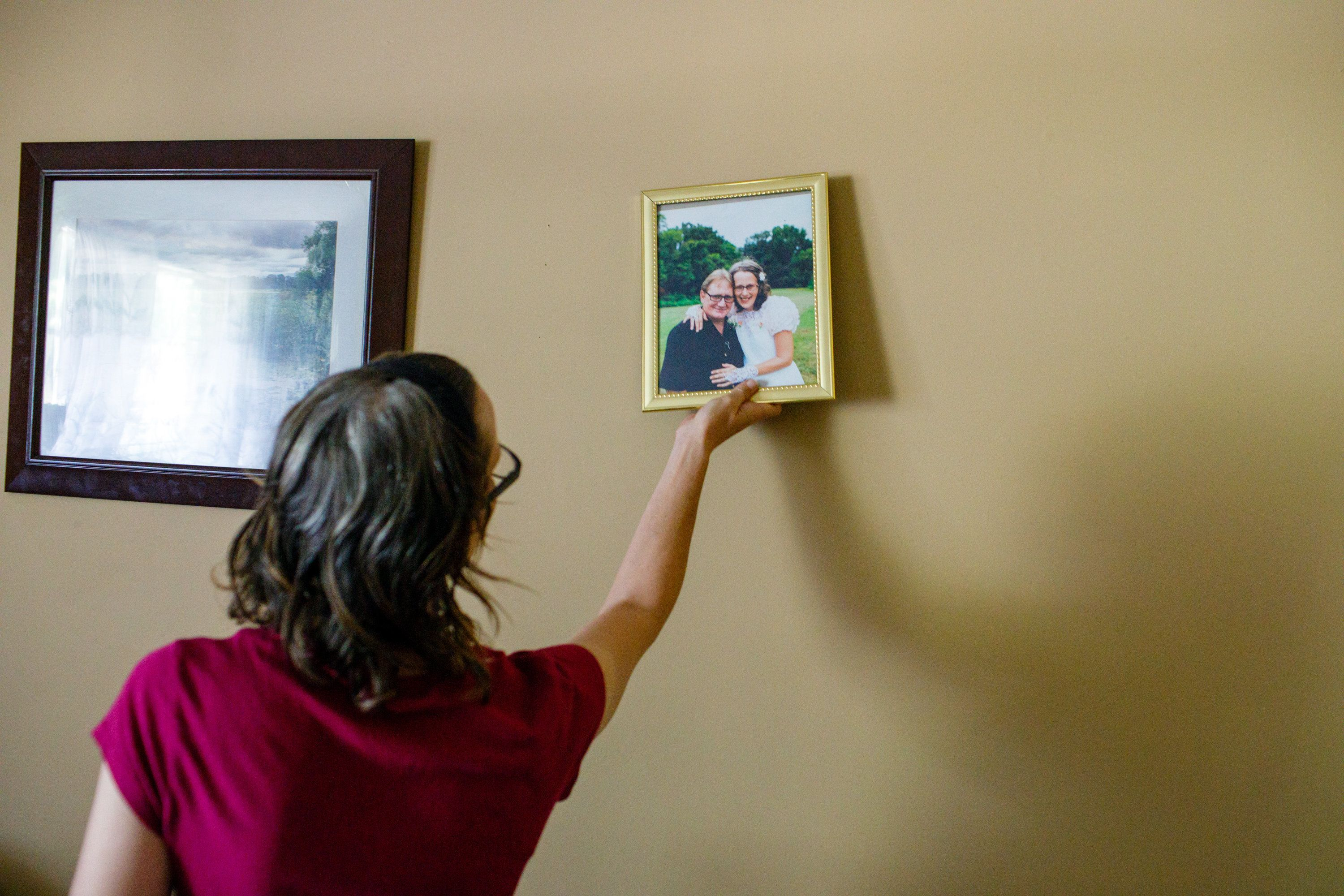 Meredith takes a framed photo of her and her husband, Jay, on their wedding day.